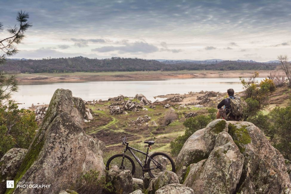 A young man sits on a rock as he takes a break from riding his mountain bike. Overlooking Doton's Cove at Folsom Lake in California.