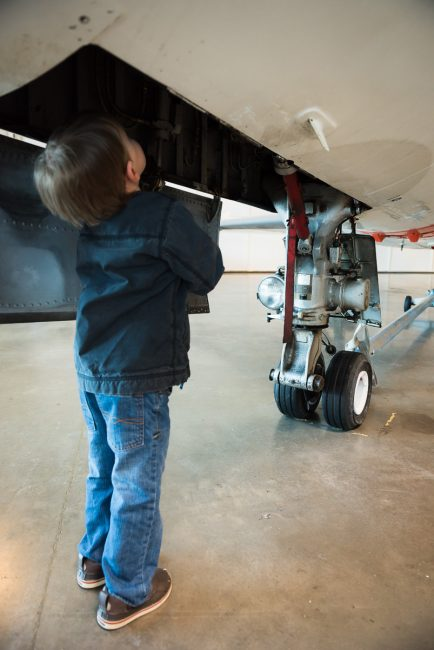 A young boy gazes up into an airplane's landing gear compartment.