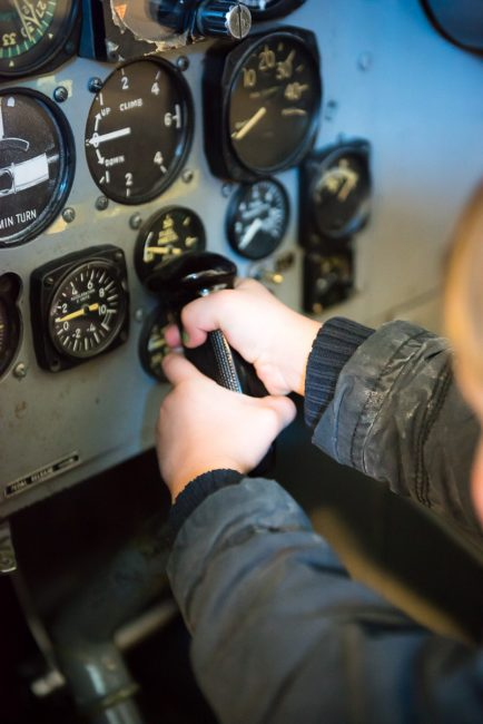 Photograph of a young boy in a plane cockpit, pretending to fly.