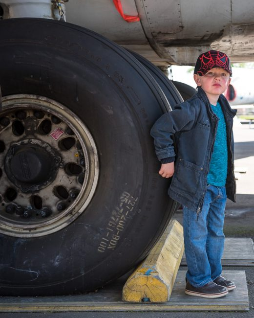 Photograph of a young boy standing by the landing gear of an airplane.