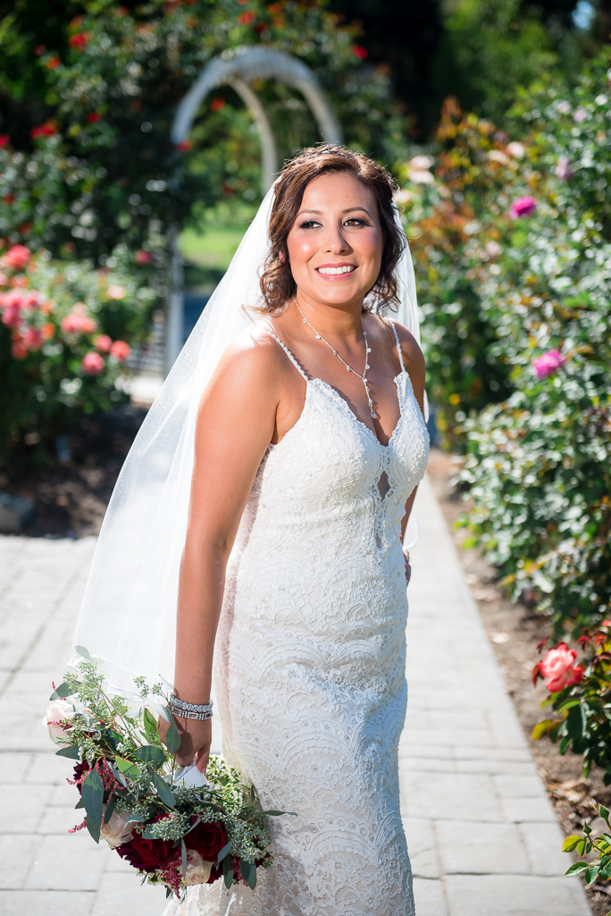 Portrait of a bride smiling as she stands in the World Peace Rose Garden in downtown Sacramento
