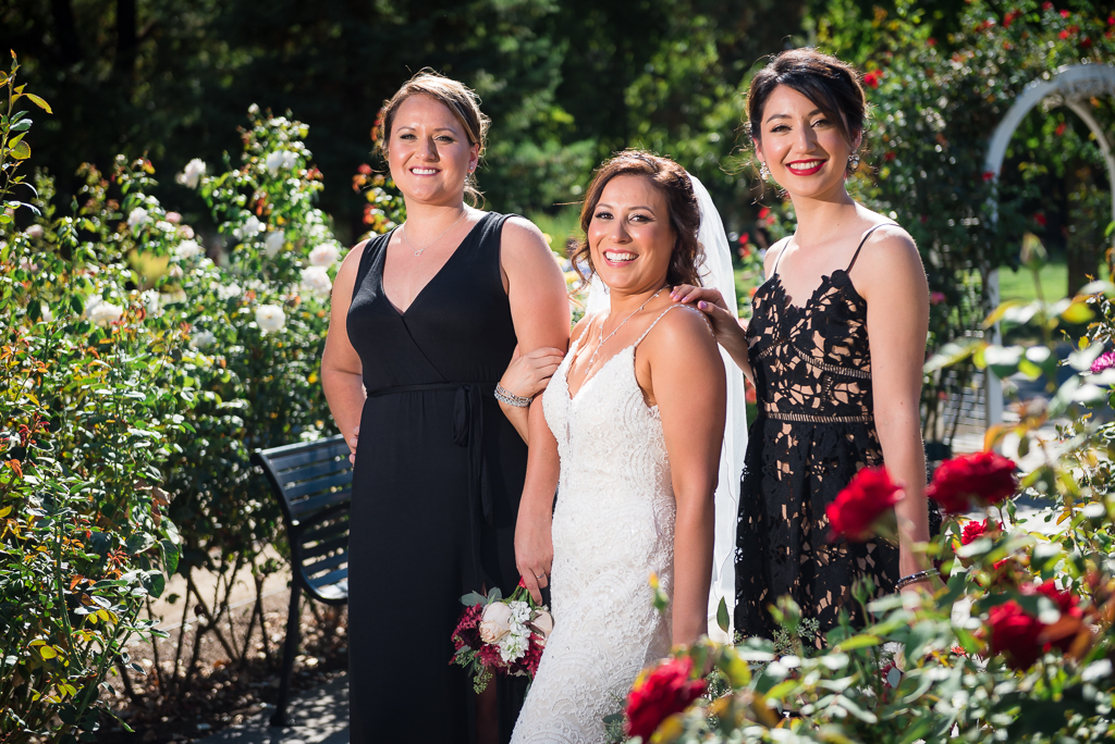 A Latina bride and her two bridesmaids pose for a portrait at the World Peace Rose Garden.