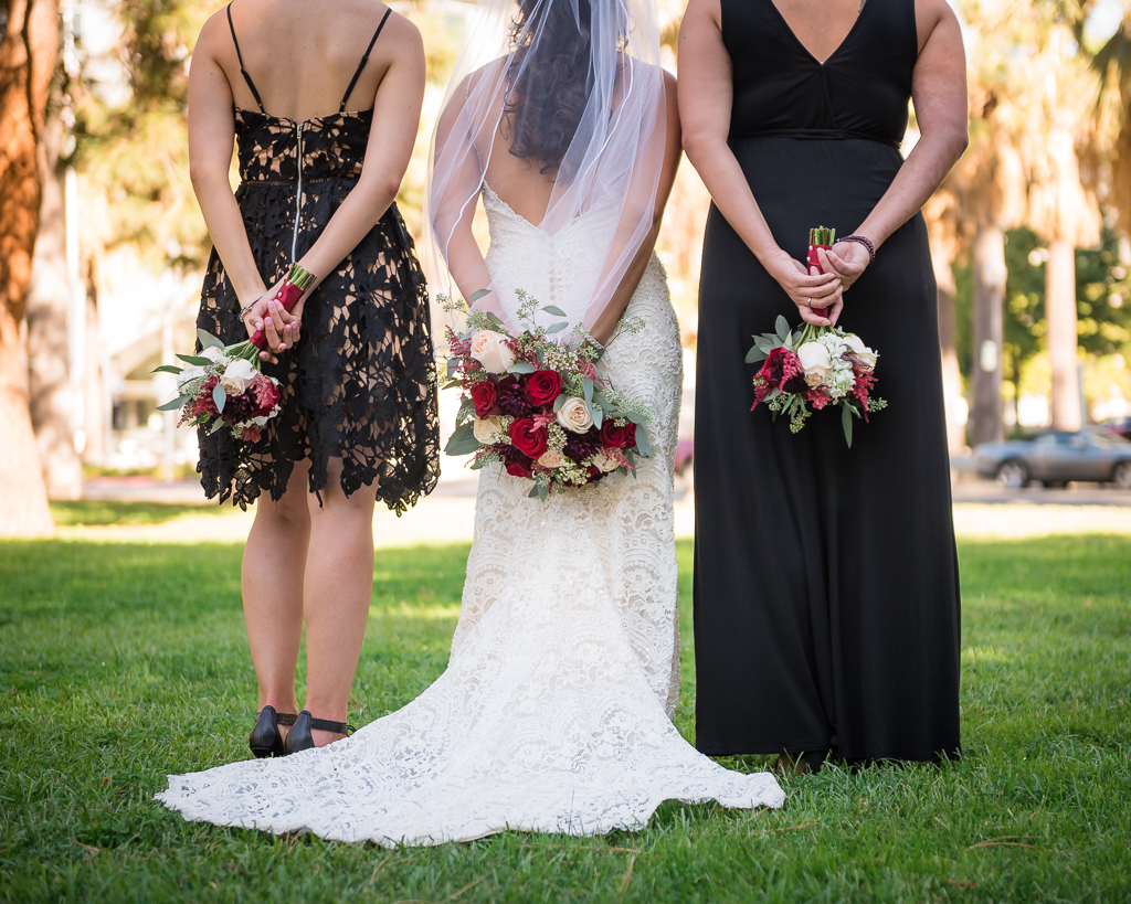 Bride with two bridesmaids holding flowers behind their waists