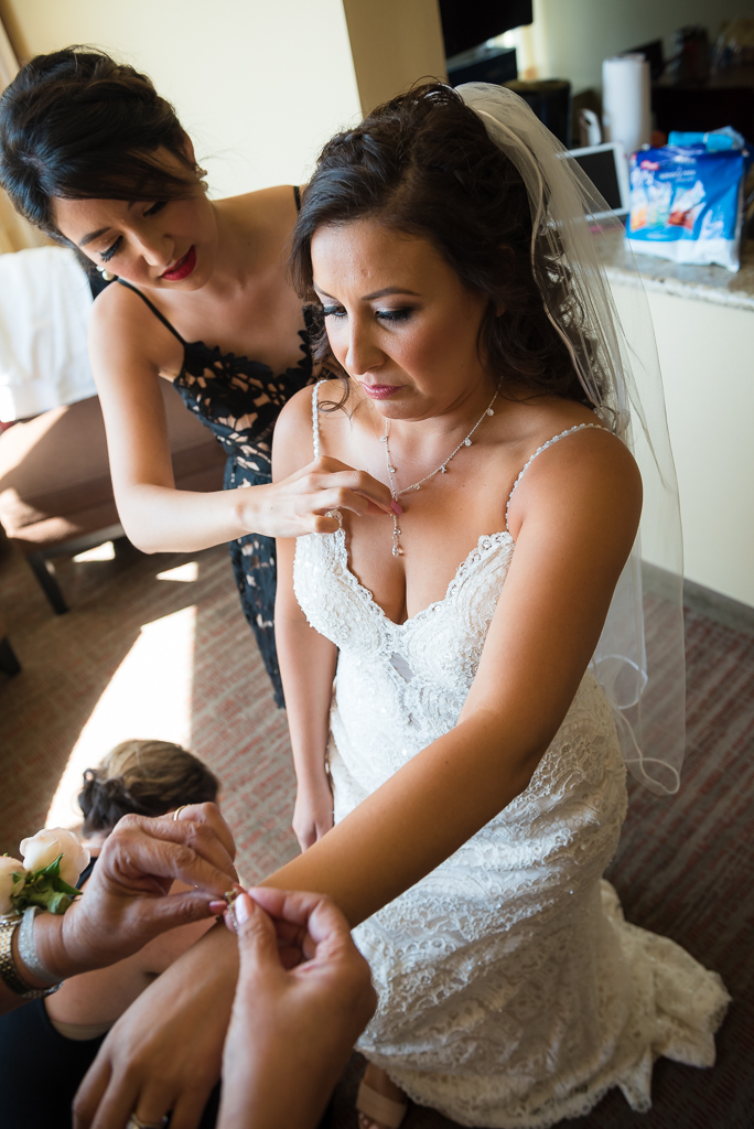 Photograph of bridesmaids helping a bride getting ready for her wedding ceremony.