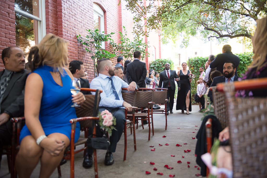 A bridesmaid and groomsman walk down the aisle to the front of a wedding venue.