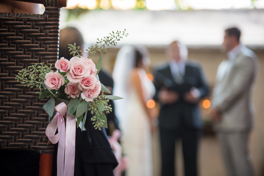 Close up of a bouquet with a wedding being officiated in the background.