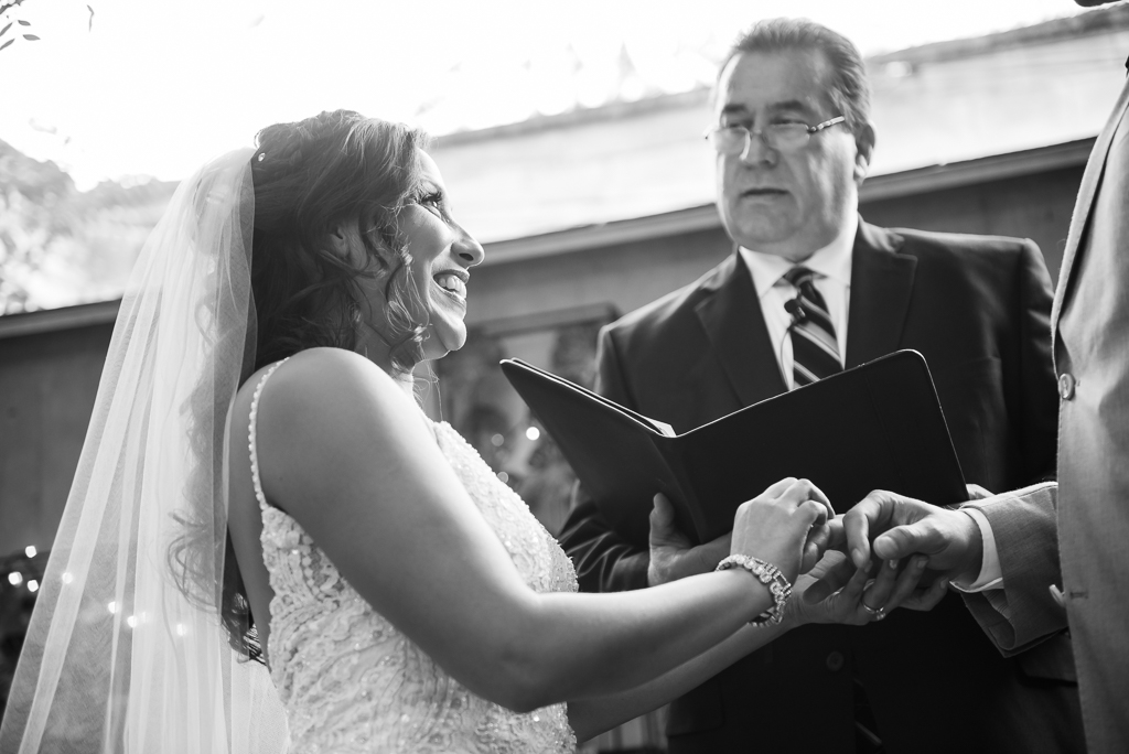 Black and white photograph of a latina bride making her vow to her groom.