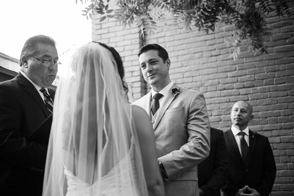 Black and white photograph of a groom delivering his vows.