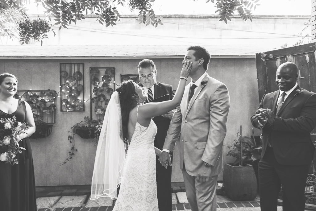 Black and white photograph of a bride wiping lipstick off her groom's face.