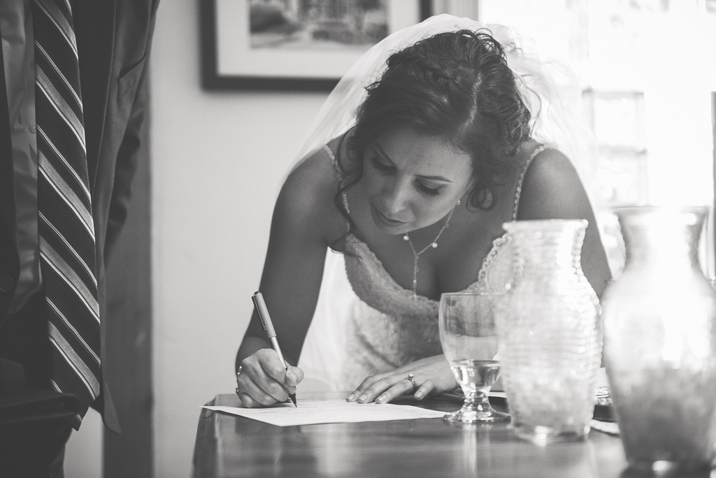 Black and white image of a bride signing her marriage license.
