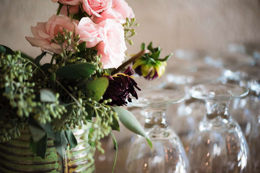 Close up photograph of a bouquet and water goblets.