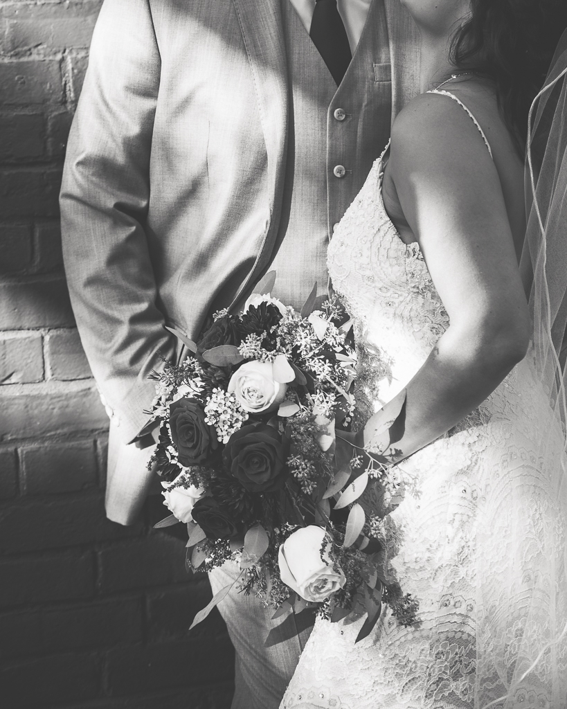 Black and white photograph of a bride and groom getting close to eachother against a brick wall.