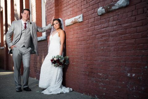 Dramatic photograph of a groom and bride standing in a brick alleyway.