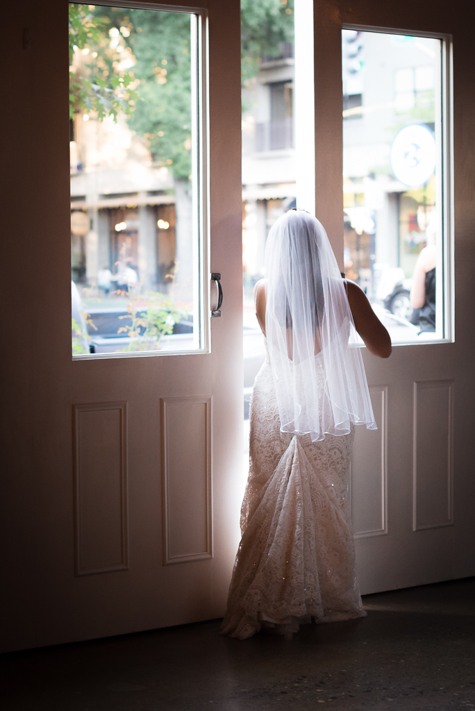 A bride opens a giant door at her reception hall, peeking out at the streets outside.