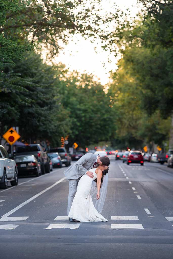 A bride and groom stand in the middle of a crosswalk as the groom dips and kisses his bride.