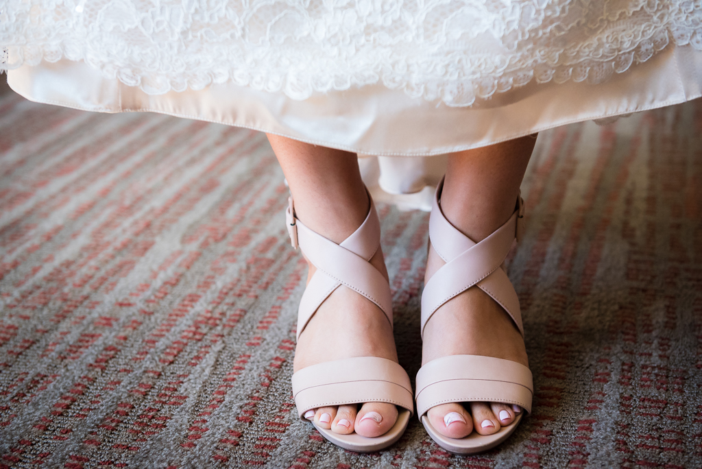 Detail shot of a bride wearing her wedding shoes, with painted nails.