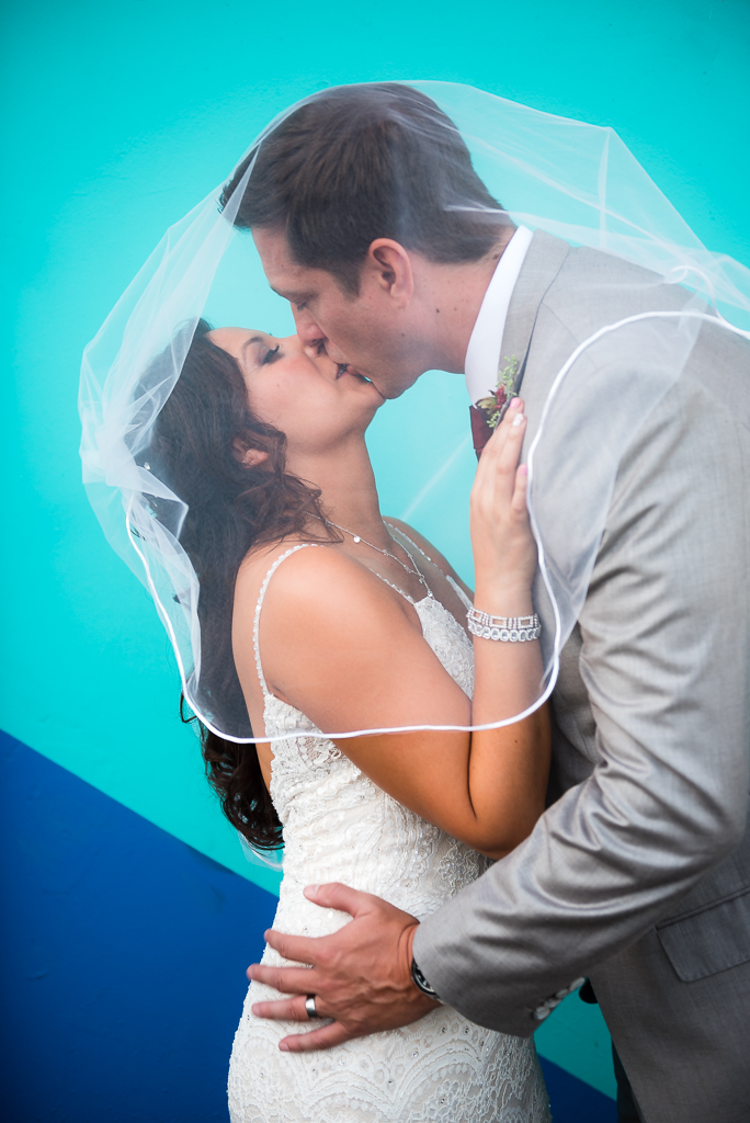 A bride and groom kiss beneath a bridal veil against a blue wall.