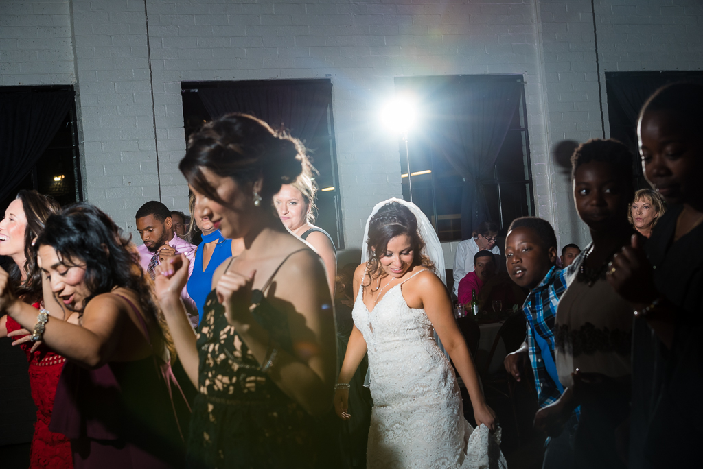 Photograph of a bride dancing in the middle of her guests at a wedding reception.