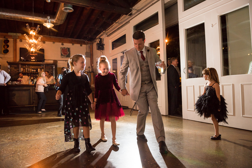 A groom teaches his nieces to dance during his wedding reception.