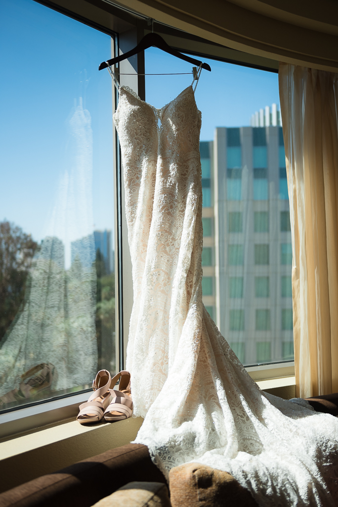 A wedding dress hangs in the window of a 10th floor hotel room