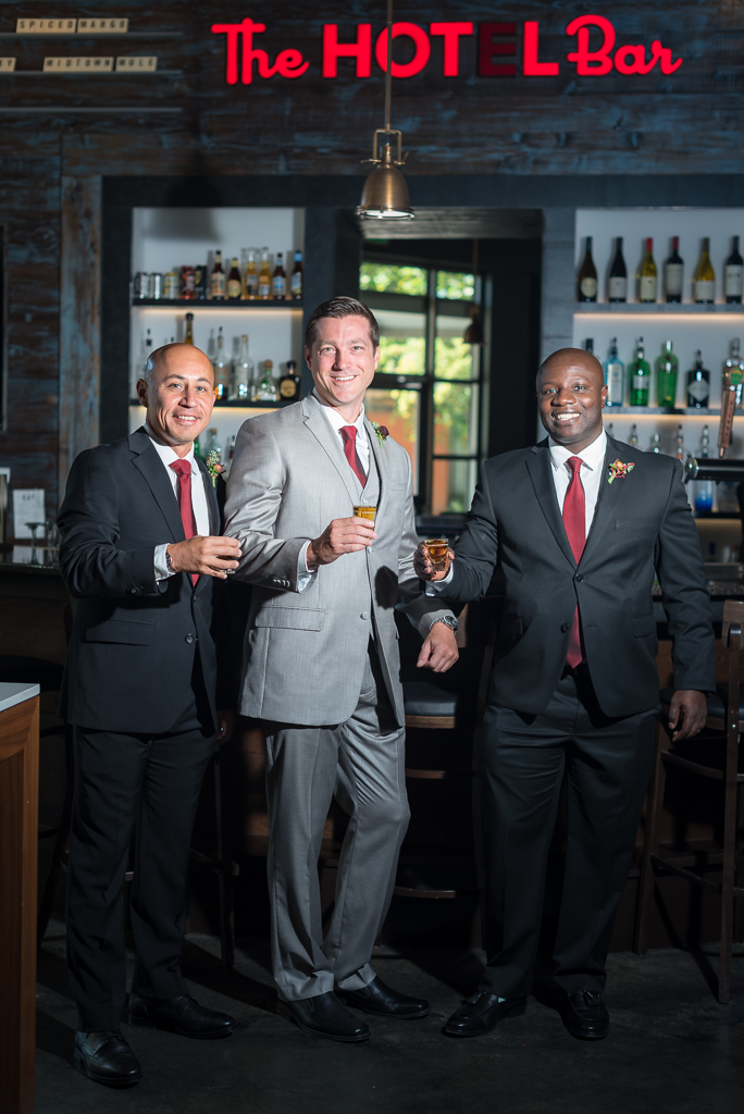 A groom and his groomsmen share some whiskey before getting on with the wedding day.