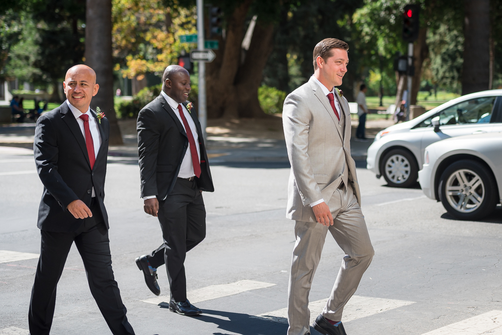 Photograph of a groom crossing the street with his two groomsmen.
