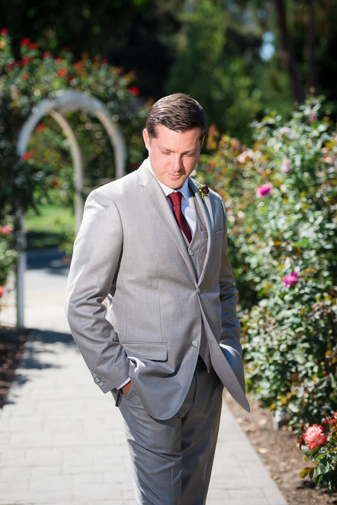 A portrait photograph of a groom in a rose garden, looking at the ground.