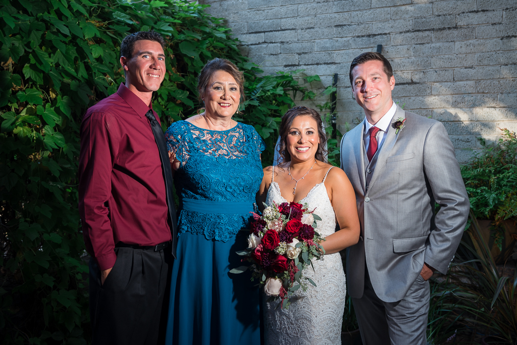 Portrait of a bride and groom with her mother and brother.