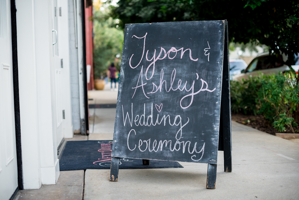 "A Sandwich board reads ""Tyson & Ashley's Wedding Ceremony"""