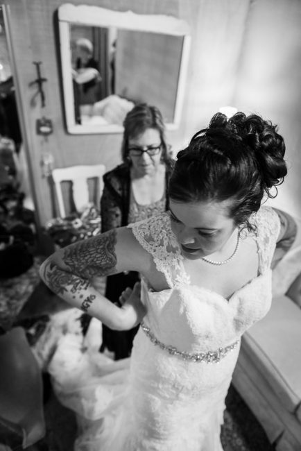 a bride gets her bustle prepared for her wedding