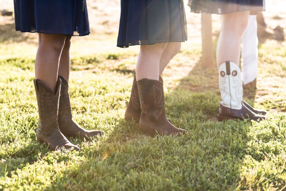 Bridesmaids each wearing boots at a country wedding.