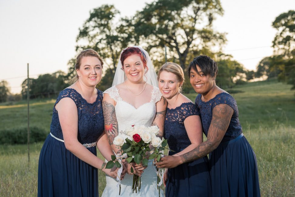 Bridesmaids gathered around their flowers during a country wedding.