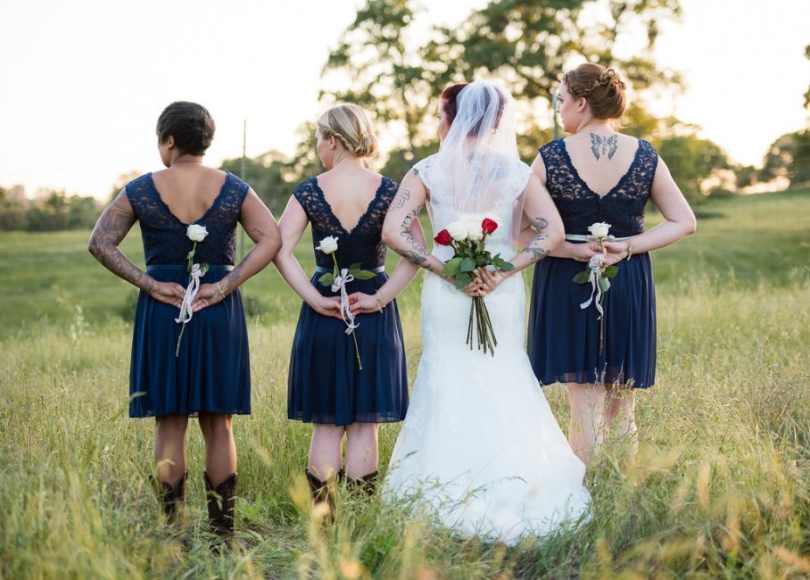 A bride and her bridesmaids clutch roses behind their backs.