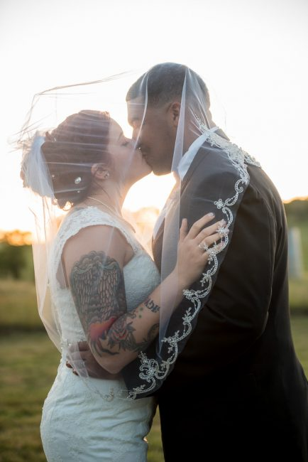 A bride kisses her groom beneath a veil at sunset in Pilot HIll, CA.