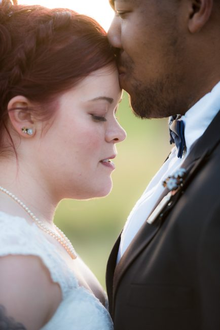 Close up portrait of a bride and her groom embracing after the wedding ceremony.