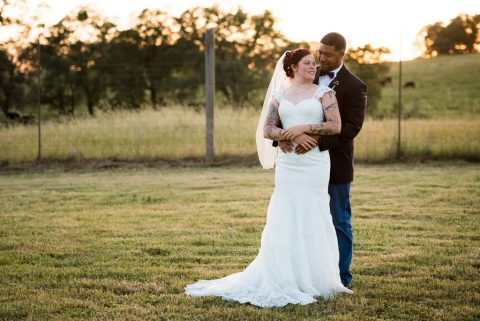 A groom embraces her bride in the field outside the Bayley Barn in Pilot Hill, CA.