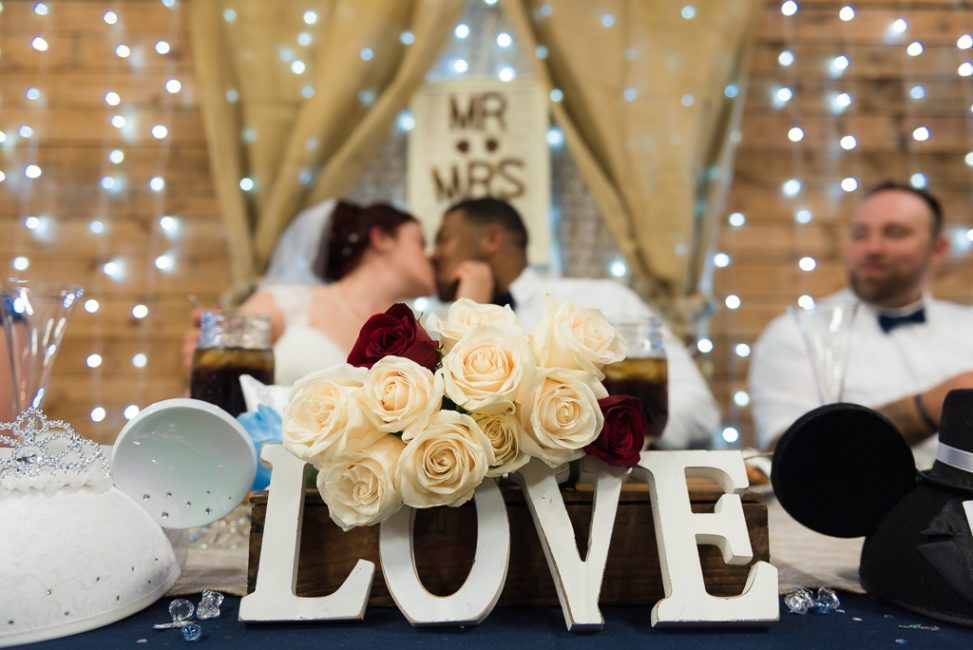 A bride and groom kiss at the head table during their country wedding.
