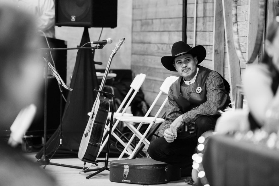 A candid photogrpah of a sheriff looking on at a country wedding reception.