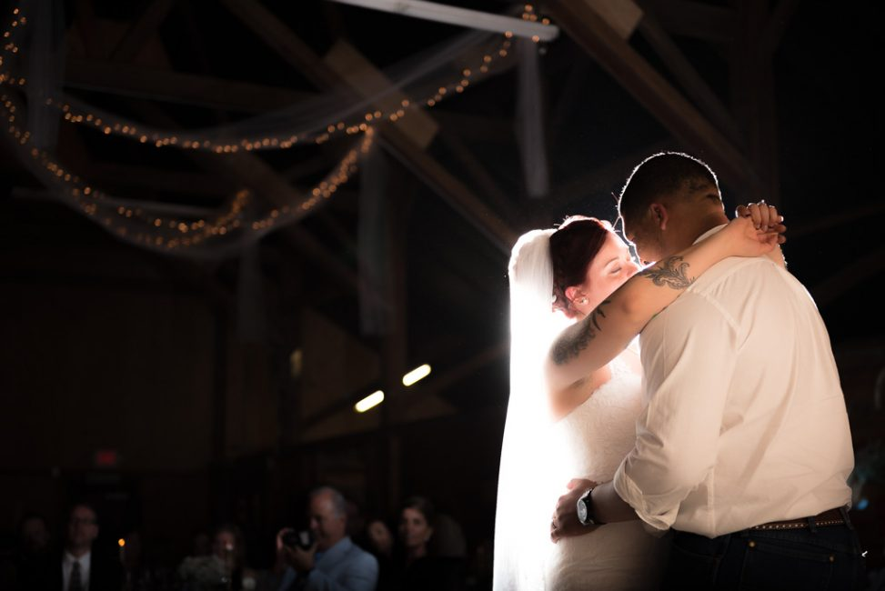 Intimate photograph of a first dance at a barn wedding.