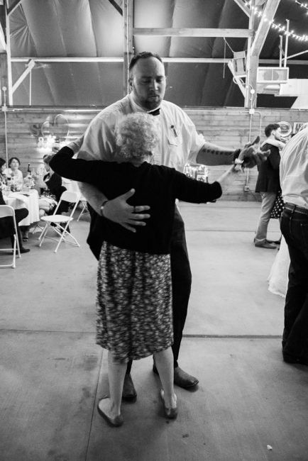 A tall groomsman dances with a short grandmother of the bride at a country wedding.