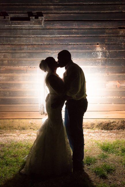 A nighttime silhouette shot of a bride and groom outside the Bayley Barn in Pilot Hill, CA.