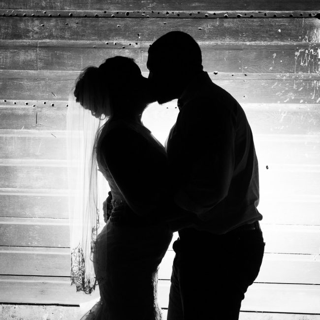 Black and white silhouette photograph of a bride and groom kissing in silhouette.