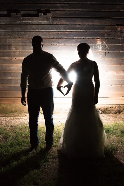 A silhouette photograph of a bride and groom making a heart outline with their hands outside Pilot Hill's Bayley Barn.