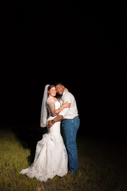 A bride and groom stand in an open field at dusk and embrace.