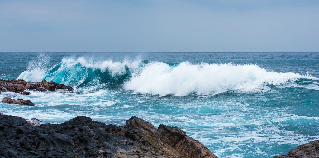 A blue wave strikes the rocky shore of Kailua-Kona.