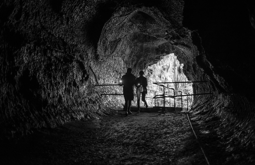 Photograph of a couple with flashlights entering the Nahuku-Thurston Lava Tube.