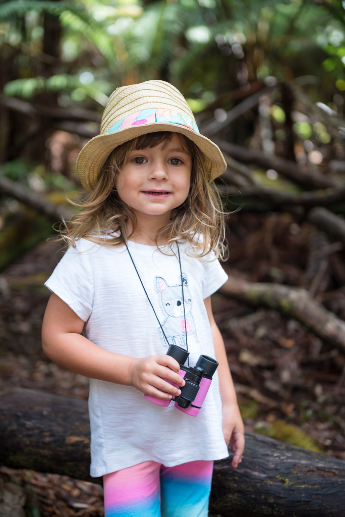 Portrait photography of a little, smiling girl clutching a pair of binoculars.