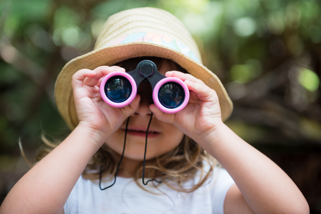 Close up photograph of a little girl holding up a pair of pink binoculars.