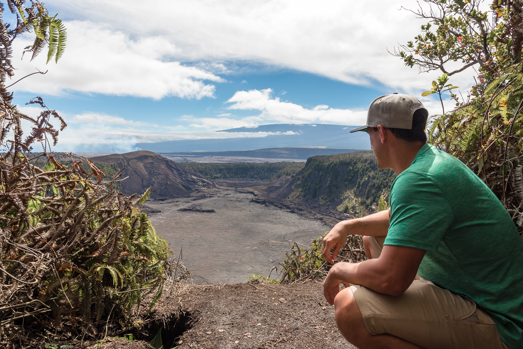 A young man looks out over Kilauea Iki crater at Hawaii Volcanoes National Park.