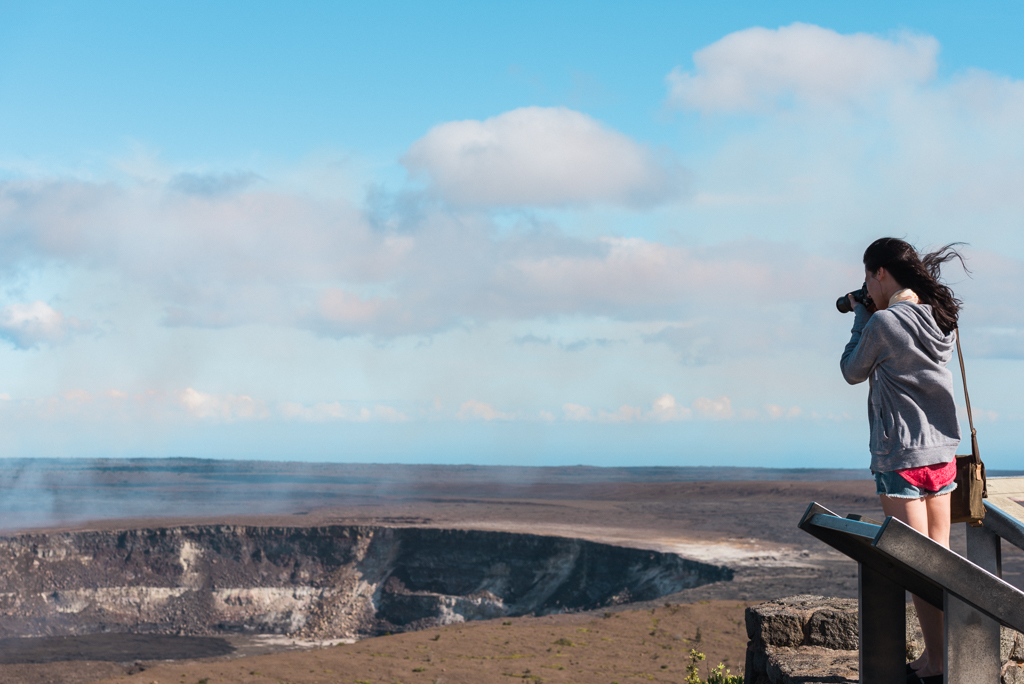 Photograph of a young woman with a camera taking a picture of Kilauea volcano.